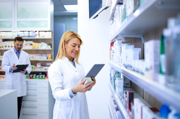 An intelligent female pharmacist checking new medicine specification online in drugstore.