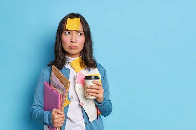 Studentessa intelligente ha un'espressione dispiaciuta seria scrive memo su adesivi di avviso coinvolti nel processo di apprendimento tiene una tazza di caffè usa e getta note informazioni sul progetto si trova sopra il muro blu