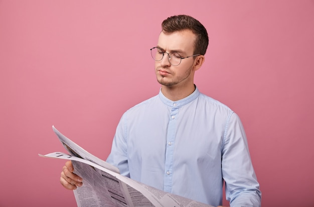 Intelligent gentleman in a pale blue shirt in glasses with a newspaper in his hands