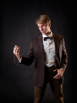 An intelligent gentleman in the victorian style. vintage retro suit, young attractive man in a vest and bow tie, he looks thoughtfully at his watch