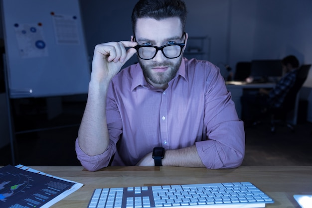 Умный вид. умный восхищенный красавец сидит за компьютером и поправляет очки, глядя на вас