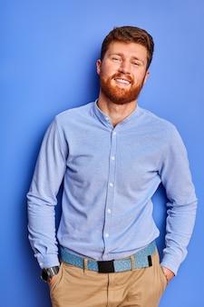 파란색 공간 위에 절연 카메라에 포즈를 취하는 셔츠에 지능형 남자, 수염을 가진 잘 생긴 빨간 머리 남성은 즐거운 미소를 가지고 있으며, 주머니에 손을 유지합니다.