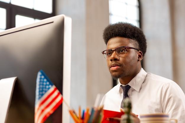 オフィスで仕事をしながらコンピューターの画面を見ている知的な男