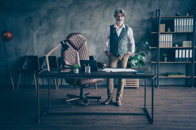 Умный старый деловой человек-юрист в костюме стоит в офисе
