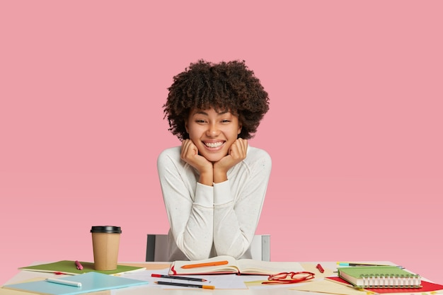 Intelligent pretty cheerful dark skinned young afro woman sits at desktop, writes reminder in notepad