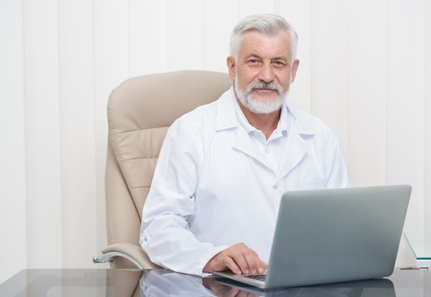 Intelligent senior doctor working on laptop in office.