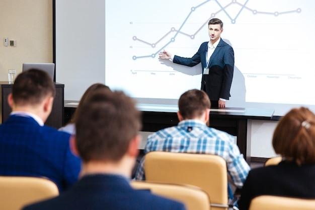 会議室でのビジネス会議で立って講義するインテリジェントスピーカー