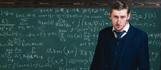 양복과 안경의 지능형 교사. 수학 공식을 설명하는 젊은 교수.