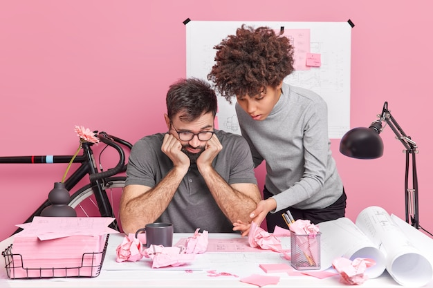 Intelligent woman and man architects try to find common solution share ideas and discuss briefing surrounded with scrumpled papers pose at desktop in home office make sketches prepare for workshop