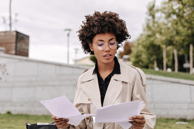 Intelligent young dark-skinned lady in eyeglasses, beige trench coat reads text and holds white paper sheets outside