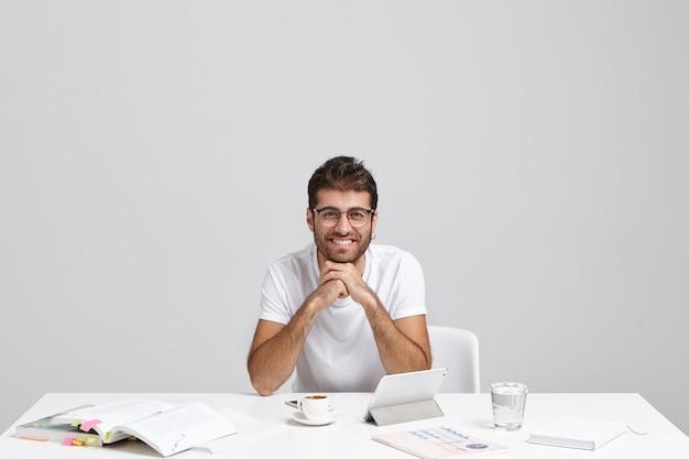 魅力的な外観を持つインテリジェントな若い男が屋内で白いテーブルに座っています。