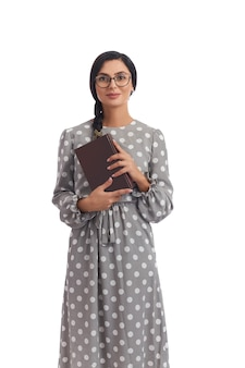 Intelligent young woman in dress and eyeglasses holding book and looking at camera