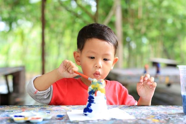 漆喰人形に小さなアジアの男の子の絵の具を意図します。