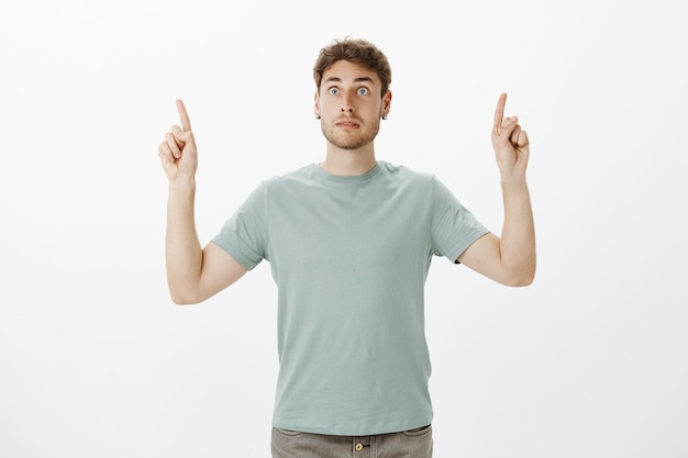Intense afraid european guy with fair hair, pointing upwards with raised index fingers and staring aside on something scary and shocking
