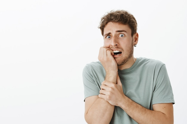 강렬한 두려워 잘 생긴 남성이 무서워하고 충격을 받고 손톱을 물고 눈이 튀어 나와