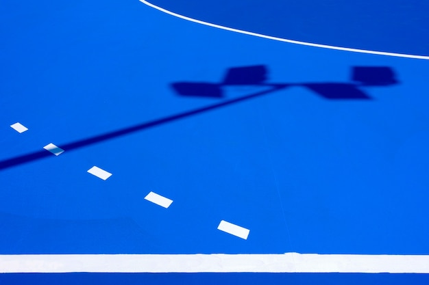 Intense blue background, from the floor of a basketball court to the midday sun, with straight lines and white curves.