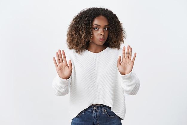 Сильно недовольная и неохотно выглядящая серьезная афроамериканка слышит тревожное предложение, хмурясь и показывая жест остановки, отказываясь и показывая отказ