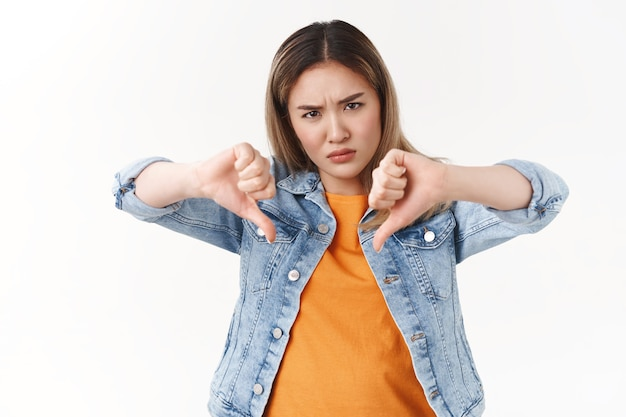 Intense displeased angry rebellious asian blond woman express disagree dislike show thumbs down hateful look unwilling see hideous behavious standing white wall
