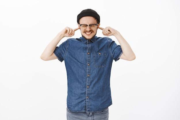 Сильный недовольный парень, испытывающий дискомфорт от плохого громкого шума, закрывающий уши, сжимая зубы и закрывая глаза указательными пальцами, стоит под фейерверком