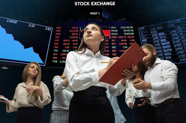Интенсивный. нервные, напряженные инвесторы анализируют кризисный фондовый рынок с графиками падения фондовой биржи. дефолт, кризис биржевых рынков и фондов. чрезмерно озабоченные люди с гаджетами, бумагами.