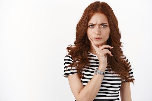 Ярко-серьезная рыжая девушка выражает сильное недоверие и сомнения, нахмуривает брови, задумчиво касается подбородка, сомневается в взгляде в камеру, обдумывает подозрительную информацию.