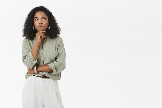 회색 티셔츠와 바지를 입은 강렬하고 똑똑하고 사려 깊은 잘 생긴 여성이 생각하면서 오른쪽 상단 모서리를 찡그린 얼굴