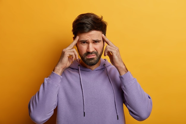 Intense unshaven guy tries to focus and recall something, keeps index fingers on temples, suffers from migraine, has dissatisfied expression, wears casual sweatshirt, isolated on yellow  wall