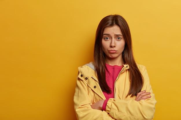 激しい動揺の女性は手を交差させ続け、興味深いチャンスを逃したことを後悔し、顔を眉をひそめ、不満を見て、ピンクのジャンパーと黄色のアノラックを着ています
