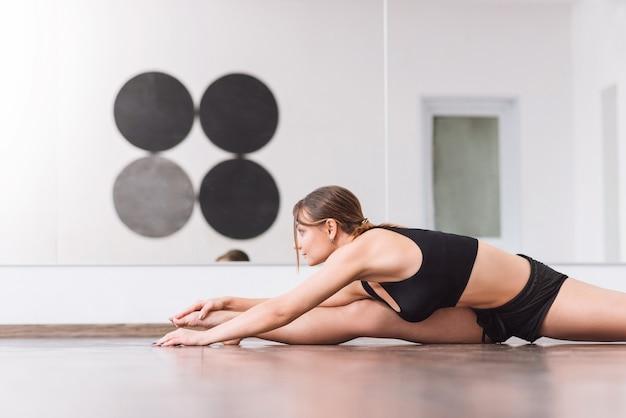 강렬한 운동. 홀에서 훈련하는 동안 분할을하고 앞으로 구부리는 젊은 전문 여성 댄서