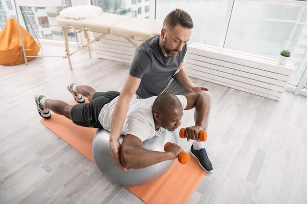 집중 운동. 그의 코치의 도움을받는 동안 아령으로 운동하는 좋은 젊은 남자