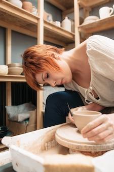 Активно работающая женщина на гончарном круге