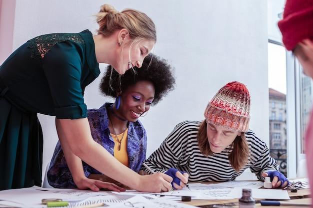 相互作用する学生。彼女の学生と対話しながら気分が良い若い美しい先生