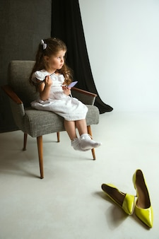 Interaction of children with adult world. cute girl trying to do bright make up for being older. little female model trying on mum's cosmetics at home. childhood, style, fashion, dream concept.