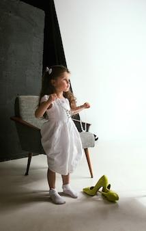 Interazione dei bambini con il mondo degli adulti. ragazza carina che indossa le scarpe oversize della mamma e il vestito per essere più grande come lei. piccolo modello femminile che prova i vestiti a casa. infanzia, stile, concetto di sogno.