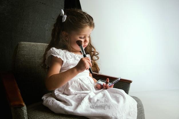 Взаимодействие детей со взрослым миром. симпатичная девушка пытается сделать яркий макияж для того, чтобы стать старше. маленькая женская модель примеряет маминую косметику дома. детство, стиль, мода, концепция мечты.