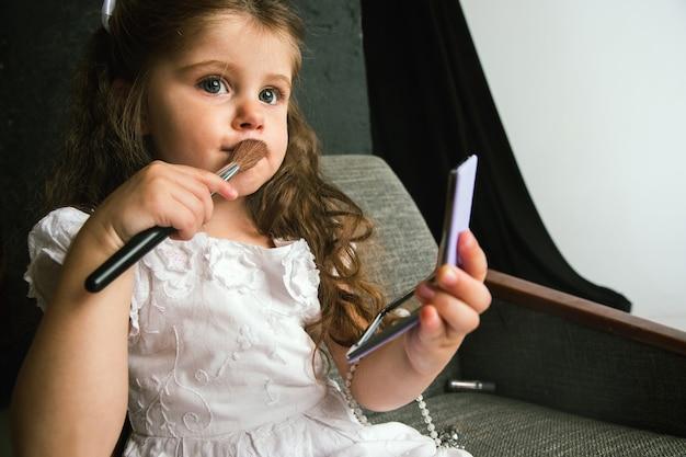 子供と大人の世界との相互作用。明るいことをしようとしているかわいい女の子は年をとることを補います。自宅でお母さんの化粧品を試着している小さな女性モデル。子供の頃、スタイル、ファッション、夢のコンセプト。