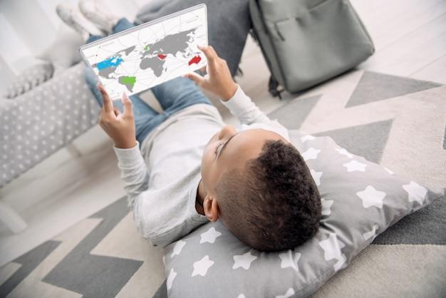 대화 형지도. 그의 뒤쪽에 누워있는 동안 태블릿을 사용하는 젊은 아프리카 미국 소년