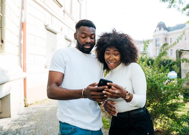 Intercultural friends looking at mobile