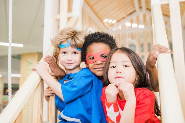 子供部屋で一緒に遊んでいる間、カメラの前の階段に座っている衣装を着た異文化の小さな友達