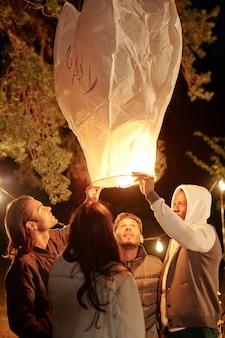 Межкультурные молодые друзья в повседневной одежде держат и смотрят на большой освещенный воздушный шар ночью, собираясь под сосной