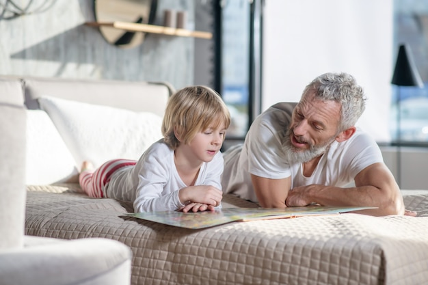Interest. gray-haired man in white tshirt reading children book and child lying on bed leaning on his hands