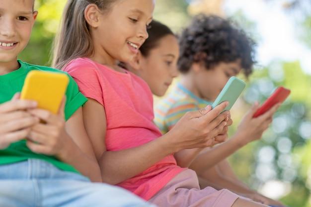 Интерес, интернет. вовлеченные улыбающиеся мальчики и девочки младшего школьного возраста пристально смотрят на свои смартфоны, сидя на улице в летний день