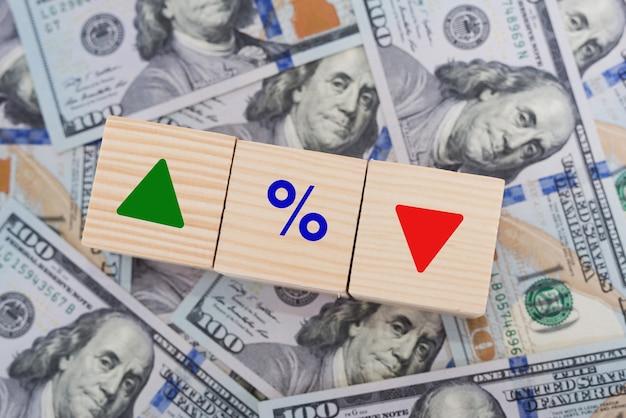 金利の金融および住宅ローンの金利の概念。パーセントアイコンとドルの上向き矢印と下向き矢印の付いた木製の立方体ブロック