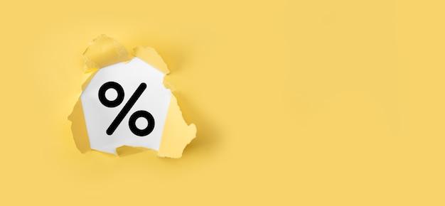 黄色の背景に金利パーセントアイコン。金利の金融と住宅ローンの金利の概念。白い背景の上のパーセントで破れた黄色い紙。