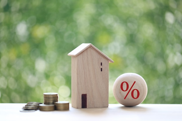 Interest rate up and banking concept, model house with percentage symbol icon and stack of coins money on natural green background, fixed rate