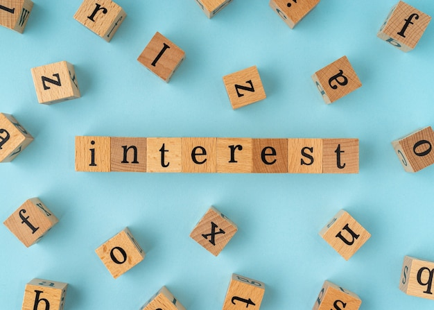 Interest word on wooden block. flat lay view on blue background.