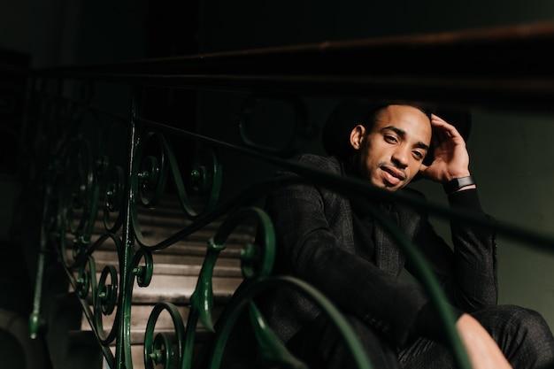 Заинтересованный африканский мужчина отдыхает на лестнице. вдохновленный парень в черном платье сидит на ступеньках и о чем-то думает.