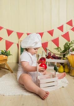 Заинтересованная девочка в шляпе и фартуке шеф-повара держит яблоки