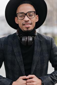 모직 우아한 재킷에 관심이있는 흑인. 어두운 피부를 가진 잘 생긴 남자의 클로즈업 초상화는 헤드폰을 착용합니다.