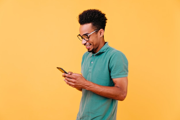 밝은 미소로 전화 화면을보고 관심있는 흑인 남자. 메시지를 읽는 안경에 잘 생긴 아프리카 소년의 실내 샷.